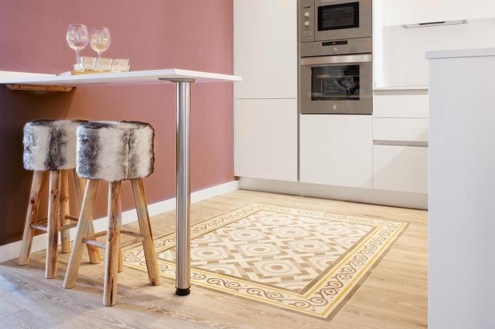 imitation carreaux de ciment, cuisine aux murs rose poudré et plancher en bois stratifié, meubles de cuisine blancs