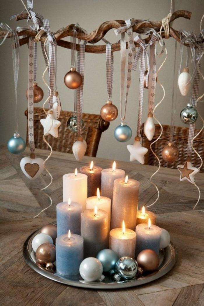 bricolage de noel, centre de table noel, créée avec onze bougies larges petites et grandes et des boules de sapin colorées, le tout posé sur un plateau rond en métal en couleur argent, branche avec des boules et d'étoiles suspendues avec des rubans aux carreaux