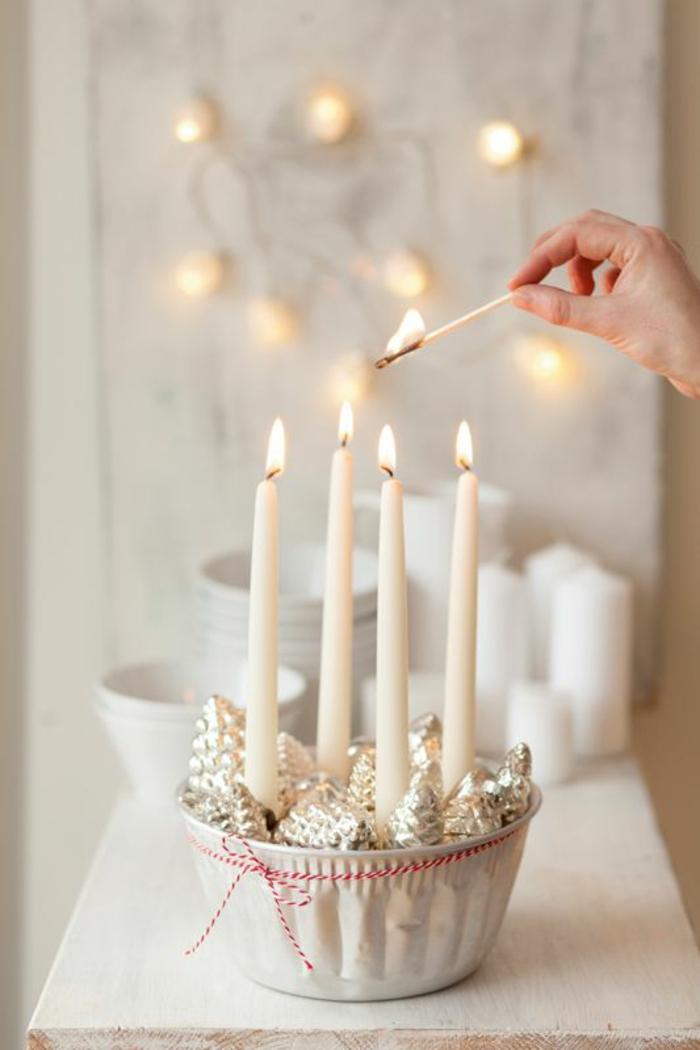 déco de noël à faire soi même facile, avec des bougies blanches et des pommes de pin décoratives pour sapin, posés dans un bol blanc en céramique, orné avec ficelle fine en rouge et blanc autour