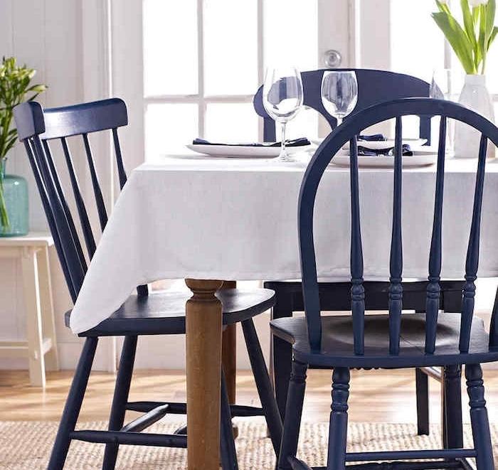 chaise relookée, exemple de chaises salle à manger repeintes e violet, table en bois, couverte de nappe blanche, tapis beige