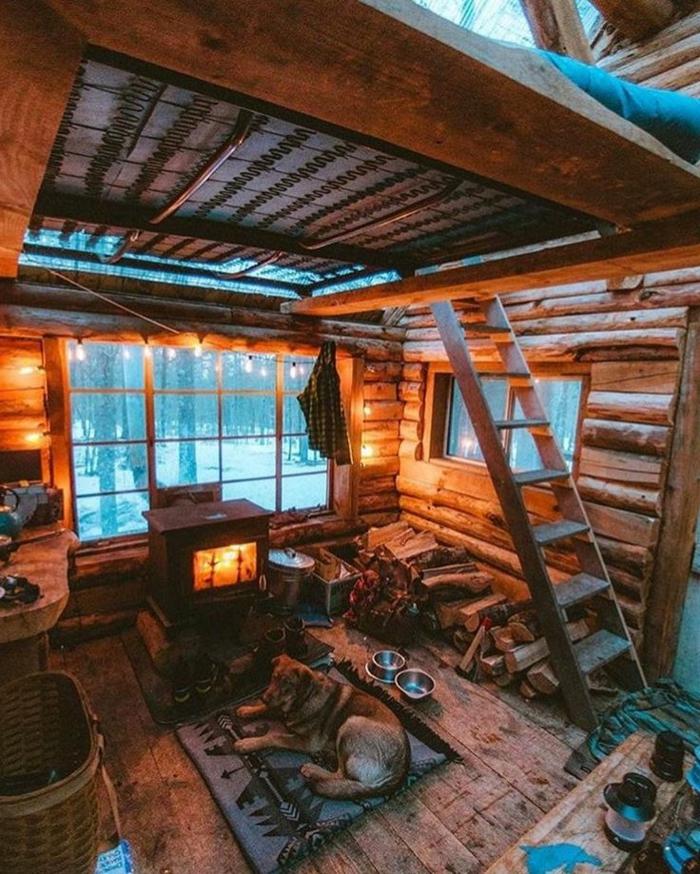 chalet dans la montagne, échelle en bois, plateforme pour lit sous la toiture