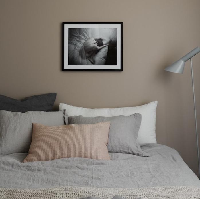 chambre à coucher couleur taupe clair, linge de lit gris, blanc et beige, mur décoré de dessin en noir et blanc, lampe grise