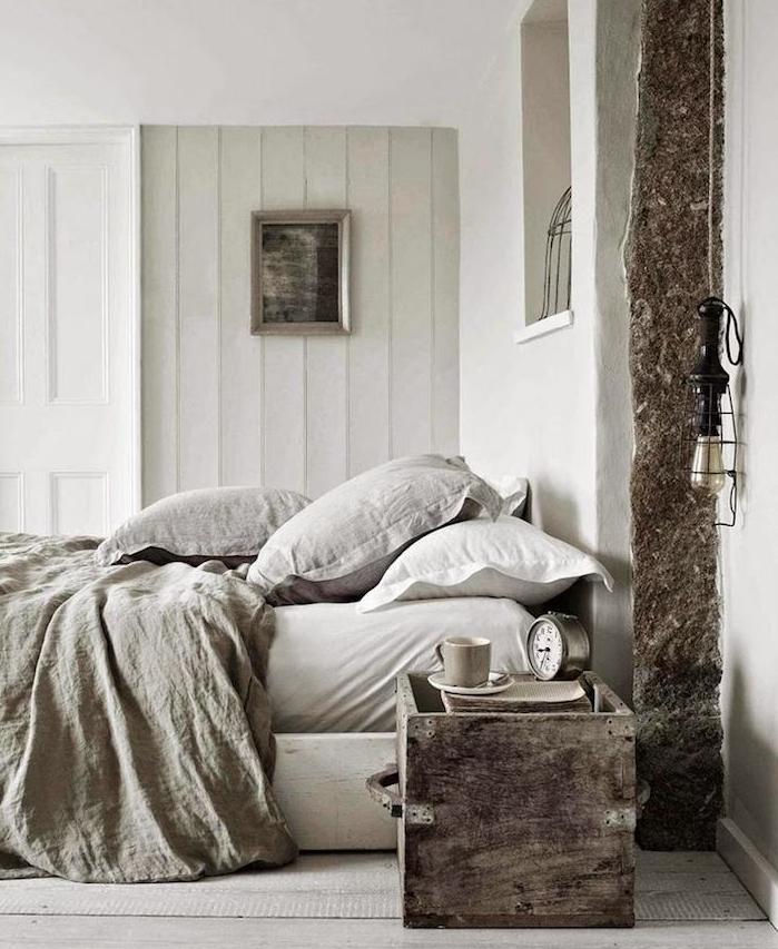 linge de lit gris taupe clair, pan de mur de lambris, table de nuit en coffre bois, poutre apparente, parquet clair, deco vintage