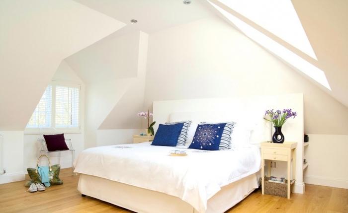 amenagement grenier, housse de coussin bleu foncé à design cosmos, petite table de chevet en bois peint beige
