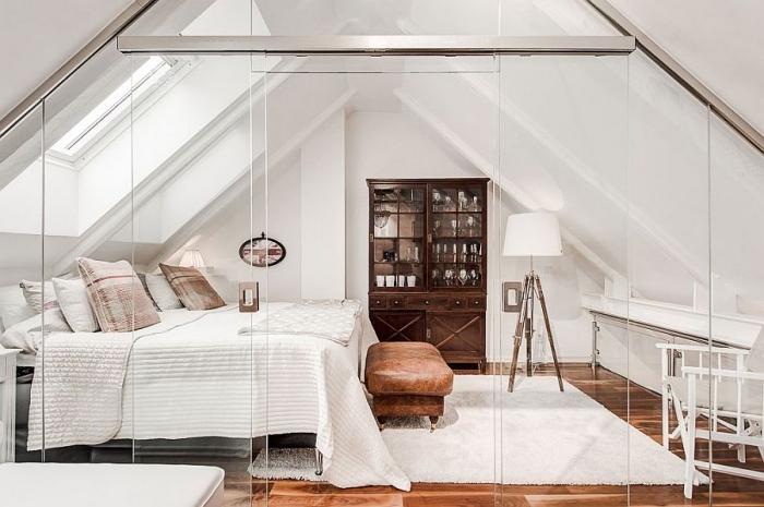piece mansardée, meubles en bois marron foncé et verre, lampe sur pied blanche avec pieds en bois, grand tapis blanc moelleux