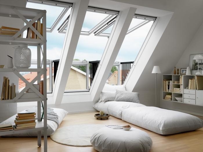 comble aménagé, petit pouf blanc avec magazine et tasse de café, tapis rond en beige, meubles en bois peints blanc