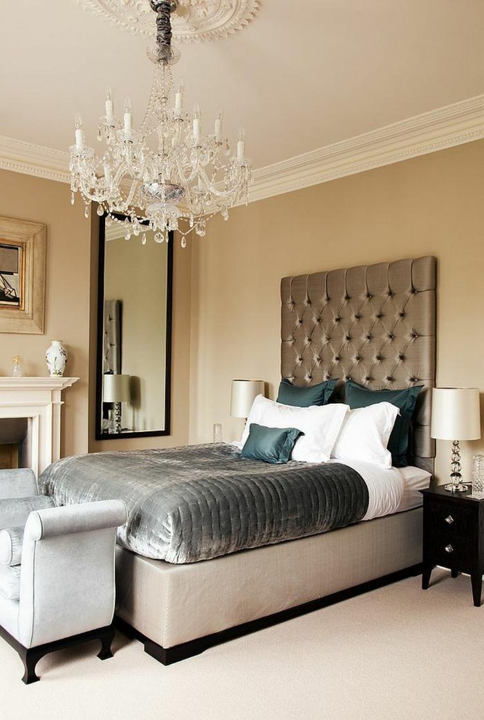 chambre baroque, un lit gris taupe, plafonnier en cristal, banquette de lit grise, cheminée décorative