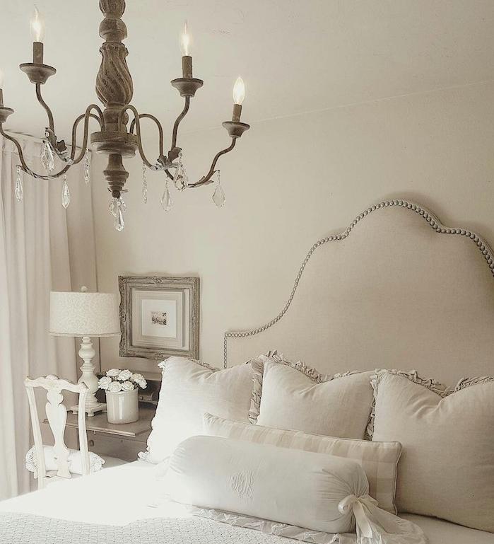 chambre gris clair à murs blancs, lustre élégant, linge de lit gris et blanc, lustre élégant style baroque, chaise blanche et bureau bois
