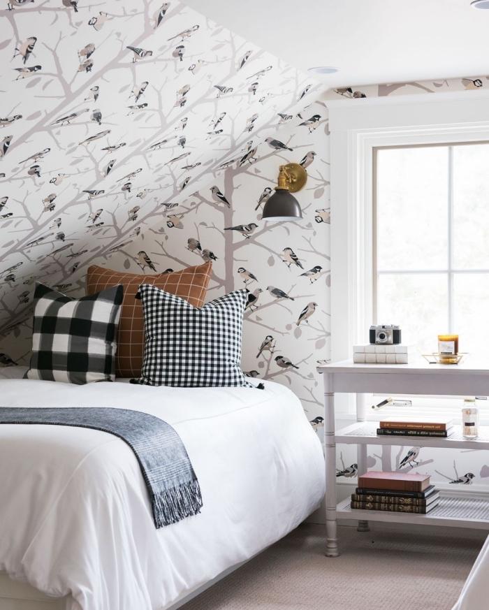 piece mansardée, modèle de papier peint blanc à design arbre et oiseaux, coussins décoratifs blanc et noir à motifs géométriques