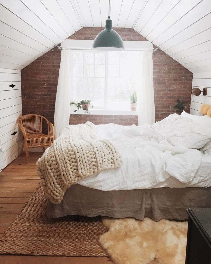 comble aménagé, chambre à coucher avec plancher en bois foncé et murs en briques rouges, modèle de lampe suspendue en blanc et vert foncé