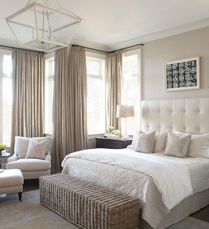 rideaux taupe couleur dans une chambre à coucher gris et blanc, bout de lit en rotin, fauteuils et linge de lit blanc et beige, lustre original