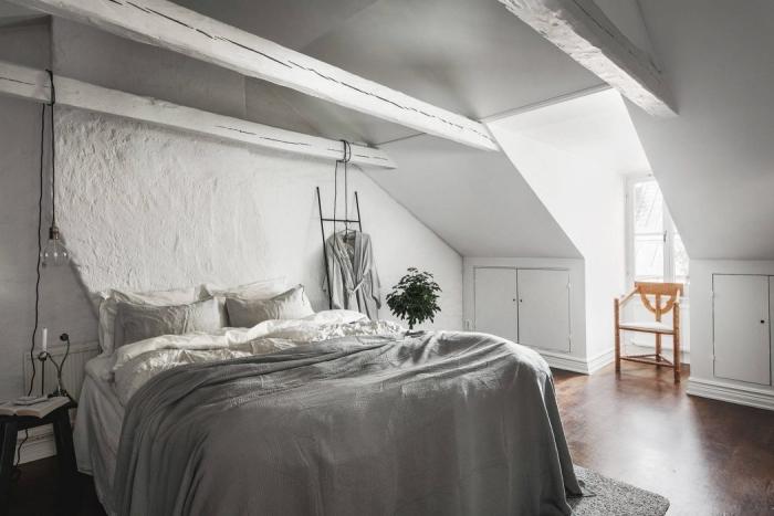 comble aménagé, chambre blanche avec poutres en bois peint blanc et plancher marron, grand lit avec couverture grise