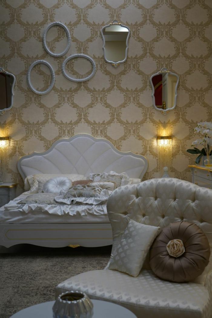 chambre romantique, papier peint baroque, lit blanc et grand fauteuil couleur crème