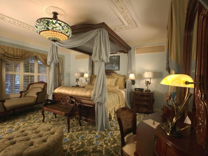 chambre romantique, tapis vert à motifs végétaux, petite banquette en bois, tabouret capitonné