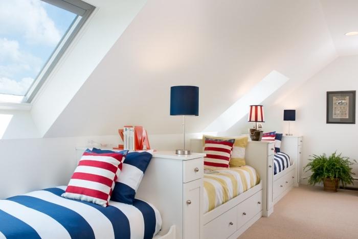amenagement grenier, linge de lit à design rayé en blanc et bleu foncé, chambre d'enfant au grenier aux murs blancs