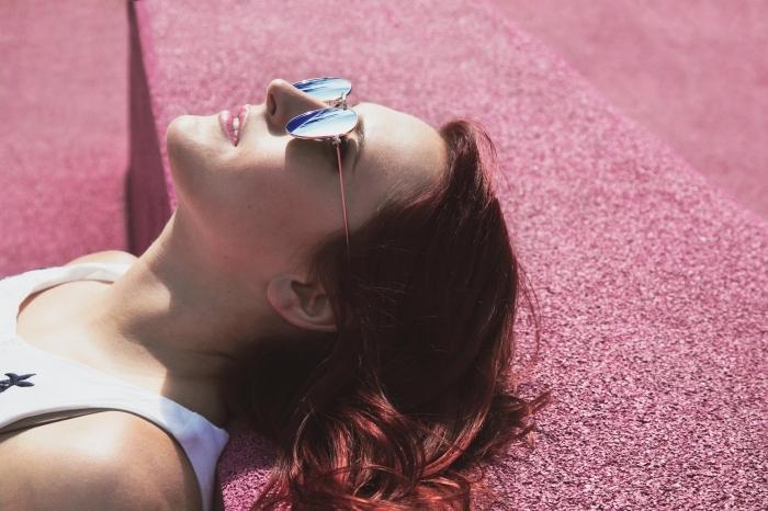 cheveux couleur auburn rouge, maquillage aux lèvres rose et fond de teint de nuance pêche, débardeur sportif en blanc avec déco en dentelle noire