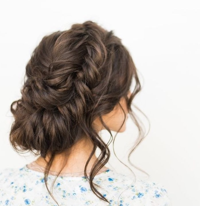 chignon flou constitué de tresse en épi avec plusieurs mèches libres sortant de partout, robe blanche fleurie, coiffure facile de noel