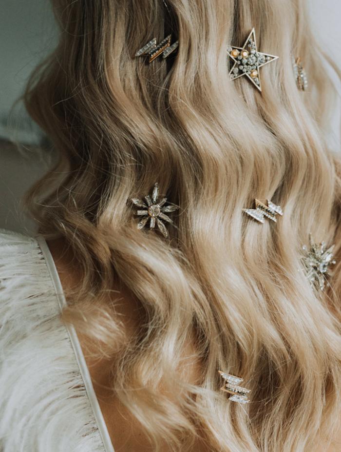 exemple de coiffure facile cheveux long, cheveux blond bouclés et accessoires bijoux pour cheveux motifs étoile, flacon de neige