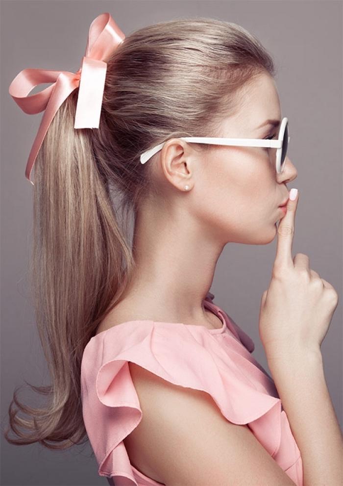 une coiffure vintage queue-de-cheval avec les pointes recourbées vers l'extérieure accessoirisée avec un ruban rose