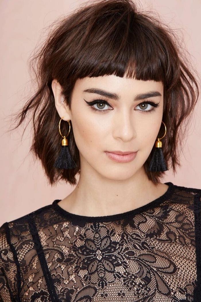 coupe cheveux mi long, modèle de robe noire en dentelle florale, boucles d'oreilles en or avec anneaux et petite cloche