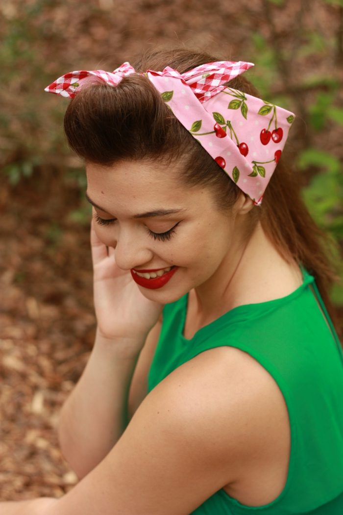 coiffure pin up avec un bandeau rose, maquillage vintage, tenue verte