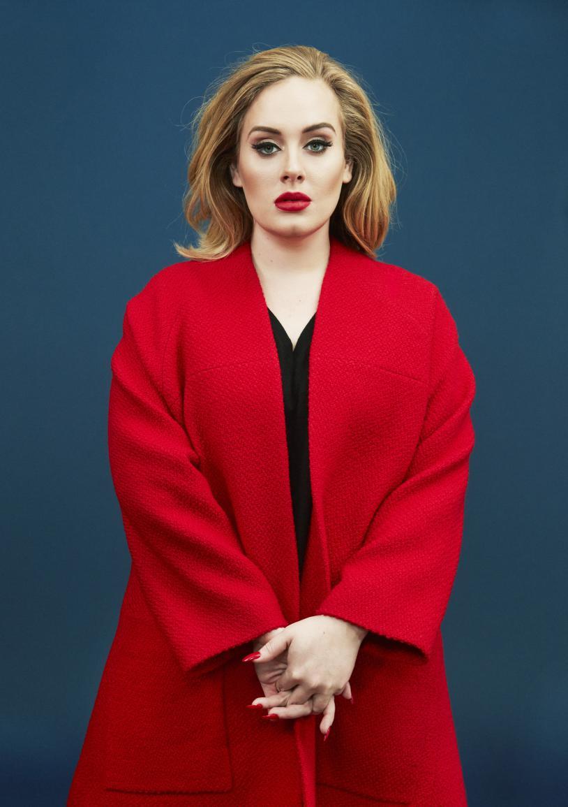 coupe pour visage rond, adele avec des cheveux lâchés avec di volume, manteau rouge et robe noire