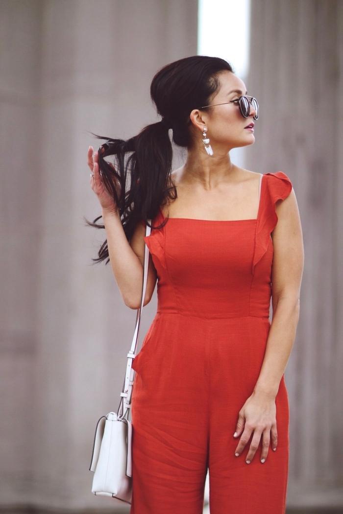 tenue de soirée femme pantalon pour mariage, combinaison rouge avec bretelles et sac à main en cuir blanc