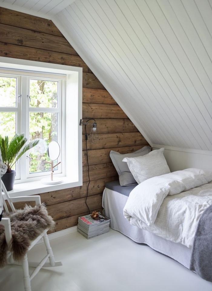 piece mansardée, chambre à coucher sous pente avec murs en bois foncé et plafond en bois peint en blanc