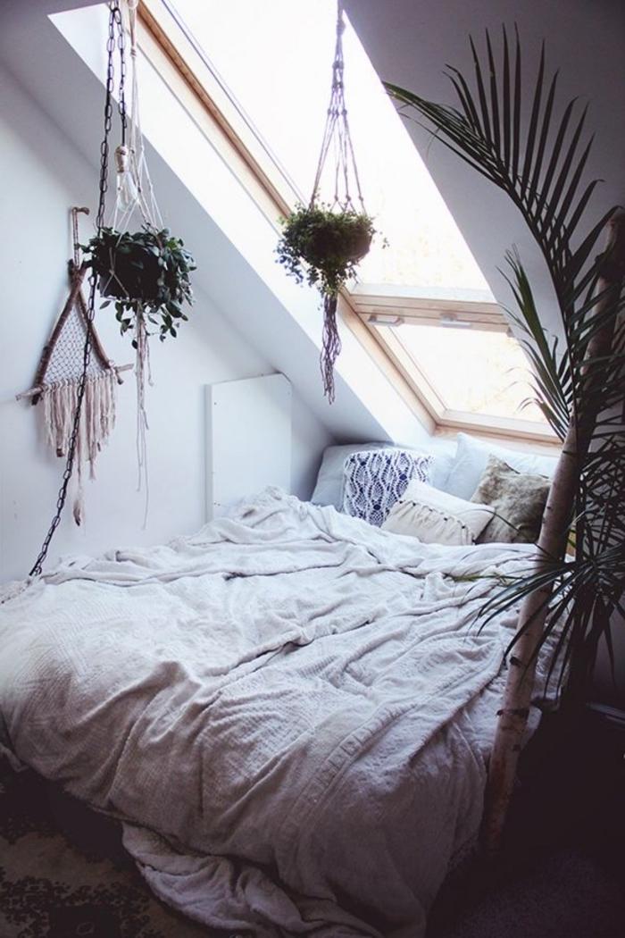 idee deco chambre mansardée, grand lit bas avec couverture blanche et coussins décoratifs doux, plantes exotiques et vertes