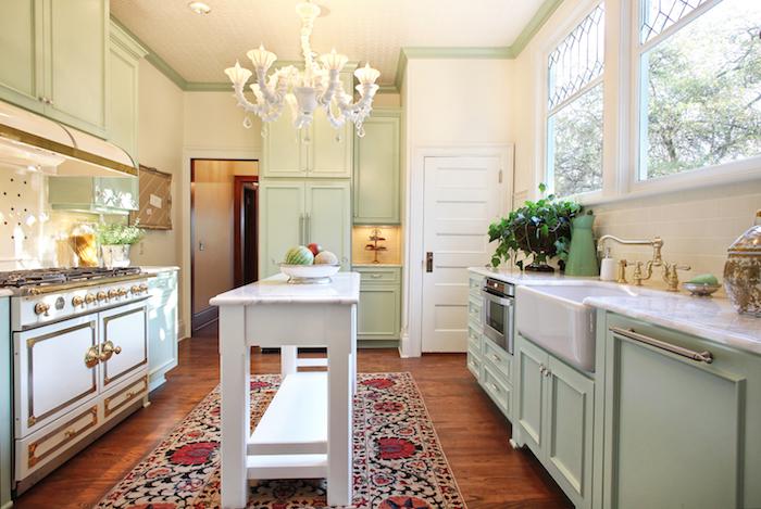 amenagement cuisine ancienne campagne en meuble cuisine vert celadon, piano de cuisson, tapis oriental, établi blanc, lustre blanc élégant