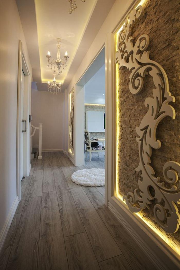 decoration couloir long et et etroit, panneau décoratif en grand motif arabesque sur toute la longueur du mur, plafond en blanc avec des frises et des luminaires en style baroque, parquet couleur taupe et petit tapis rond blanc imitation fourrure