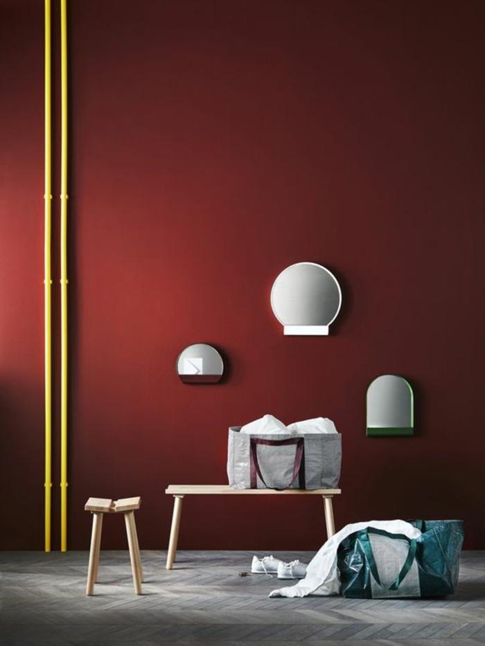 idée entrée avec des murs en rouge rubis et éléments en jaune, sol recouvert de parquet en gris foncé et clair, banc en bis clair, petit tabouret en bois clair, trois appliques murales en blanc, en formes rondes