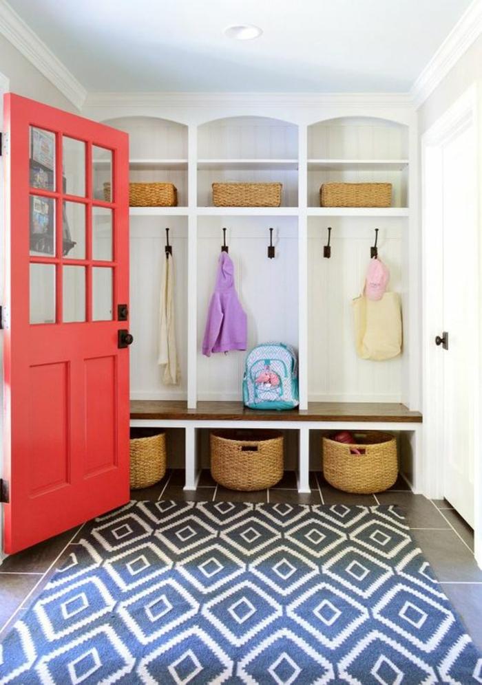 quelle couleur pour un couloir, tapis en bleu et blanc, porte en corail, murs en blanc, carrelage en gris clair, espaces de rangement en forme de niches et d'étagères blanches, patères en métal noir dans les niches