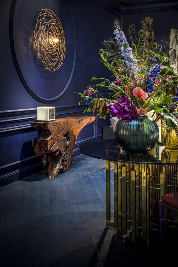 deco couloir en bleu électrique avec frise taille grande et en forme ronde illuminée par une ampoule, table design en forme de tronc d'arbre stylisé, grande table ronde en verre trempé et en parties métalliques dorées
