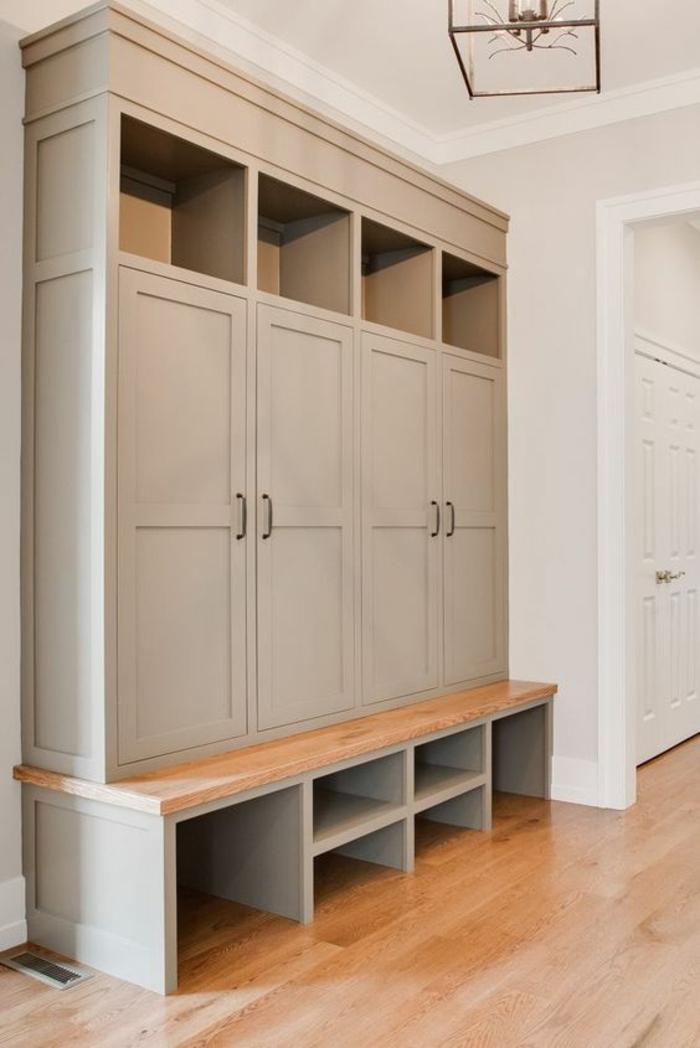 decoration couloir gris et blanc, grand meuble avec quatre battants et quatre niches de rangement sur sa partie supérieure, armoire posés sur un banc en gris clair et beige, avec des étagères de rangement en-dessous, parquet PVC imitation bois, luminaire carré en métal et verre style art déco