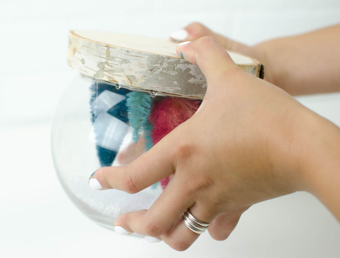 comment faire une boule à neige originale à motif forêt avec rondin de bois comme support et des sapins décoratifs multicolores à l intérieur