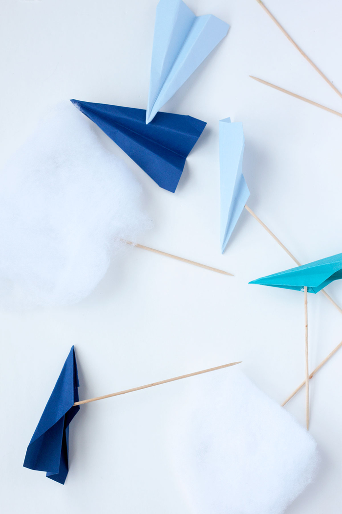 des avions en papier coloré transformés en jolis cake toppers pour décorer un gâteau d anniversaire sur thème voyage