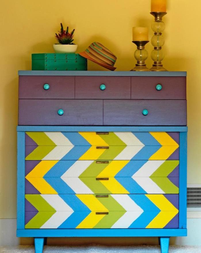 idée pour customiser un meuble, motif flèches colorées en vert, jaune, gris et bleu avec poignées vintage, decoration retro chic de bougeoirs, boite et chapeau