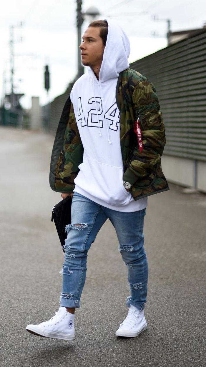 look décontractée à inspiration streetwer qui associe la veste camouflage homme à un sweat à capuche oversize et des jeans déchirés
