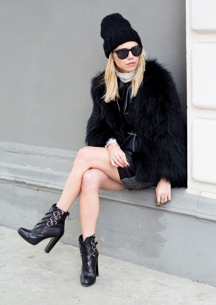 style vestimentaire femme, look élégant avec jupe courte en cuir noir et manteau en faux fur noir, bottines à talons hauts avec bonnet en crochet noirs
