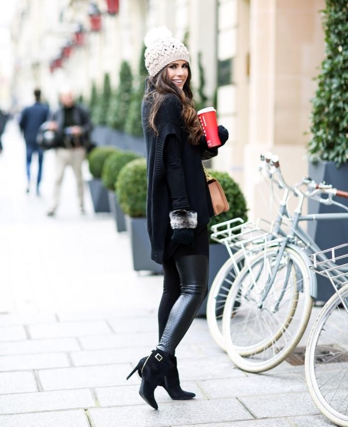 femme bien habillée, look élégant et féminin en pantalon de cuir noir et gilet noir, bottes à talons noires combinées avec bonnet en crochet blanc