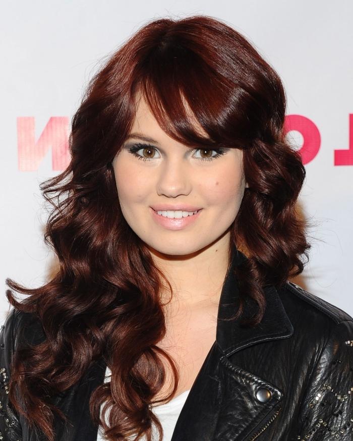 couleur auburn foncé, coiffure pour cheveux longs et bouclés avec frange sur le côté, maquillage aux lèvres rose et yeux smoky