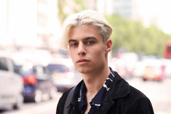 une coupe cheveux homme inspirée des années quatre-vingt-dix avec raie au milieu des cheveux et une coloration blonde
