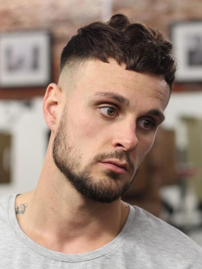 une coupe dégradé homme avec une ligne de démarcation bien nette et une frange courte coiffée sur le devant