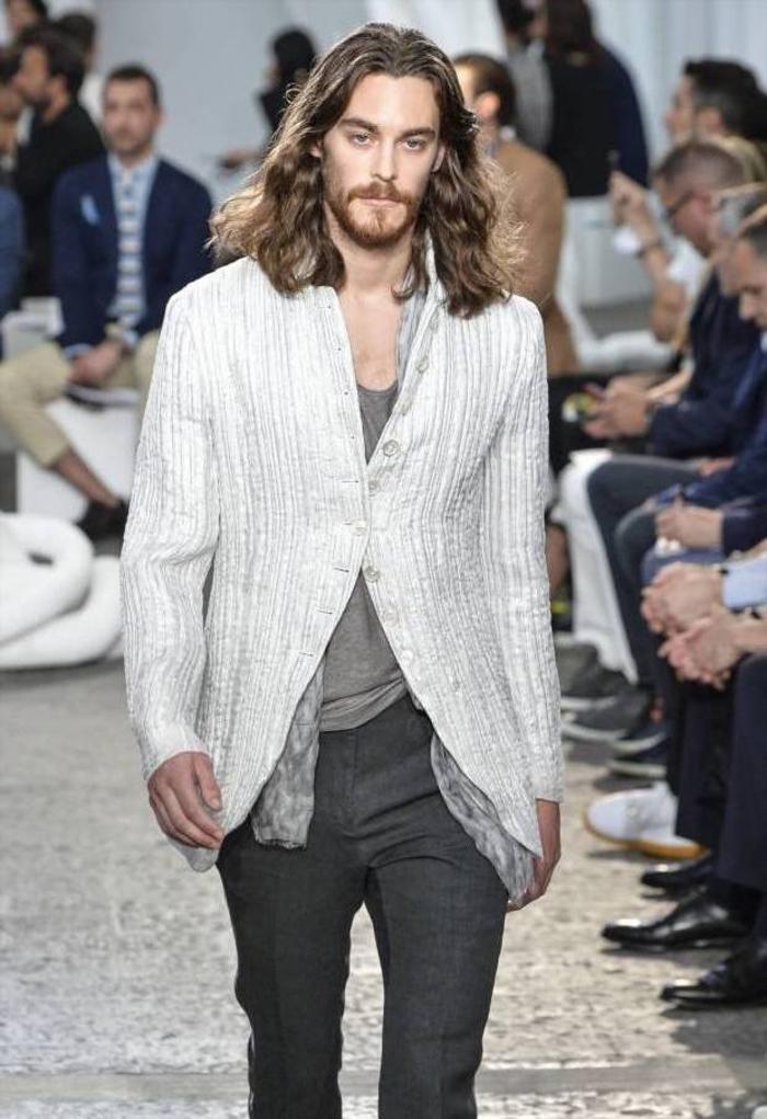 une coiffure homme pour cheveux longs avec raie tracée au milieu et des mèches souples à effet naturel