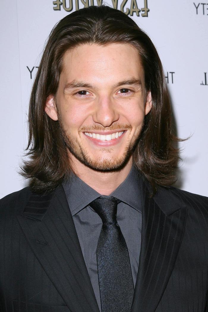 une coiffure homme assez versatile pour des cheveux mi-longs avec une raie au milieu et des années quatre-vingt dix