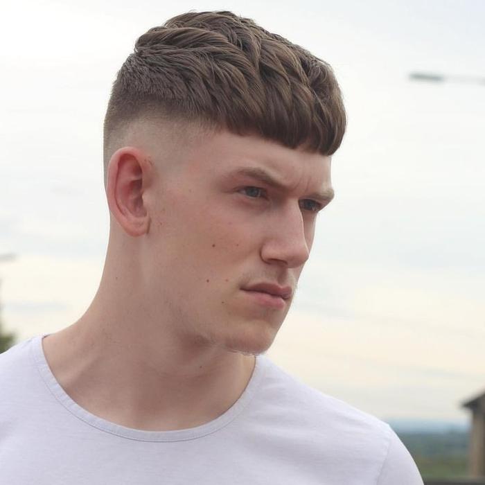 une coupe de cheveux homme court avec frange droite et une démarcation nette entre le bas rasé et les cheveux plus longs sur le dessus