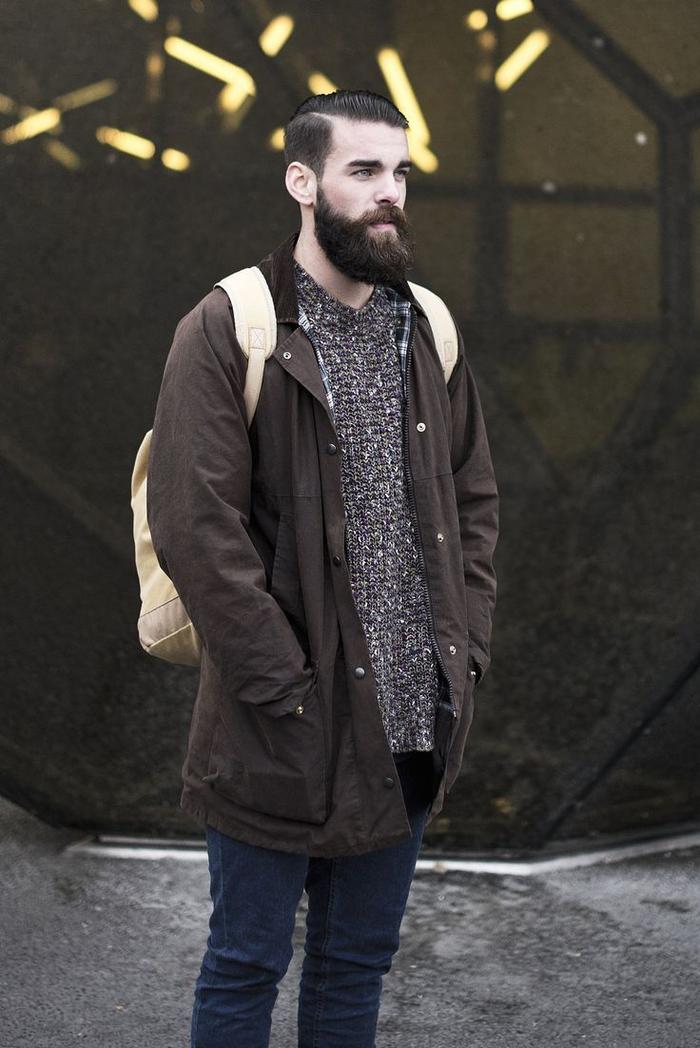 une coupe hipster de viking moderne avec undercut, barbe bien fournie et des cheveux gominés en arrière