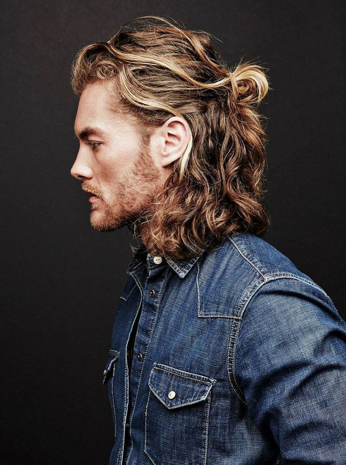 une coupe hipster à cheveux mi-longs bouclés attachés en demi-queue de cheval