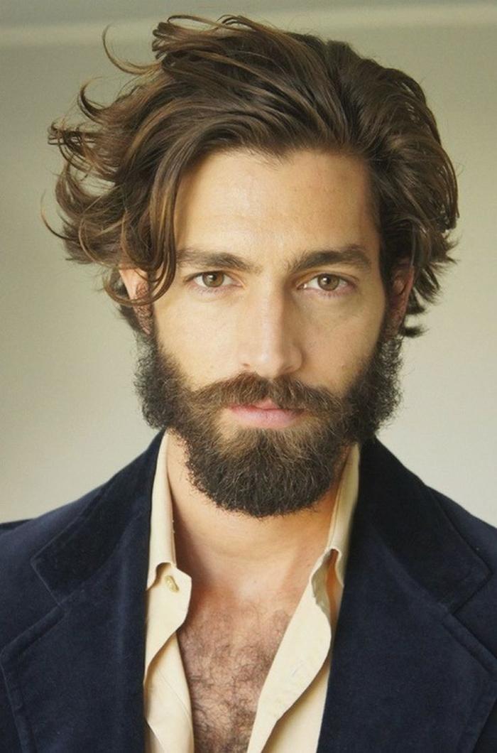 une coiffure homme d'un look ébouriffé et des mèches mi-longues souples coiffées en arrière